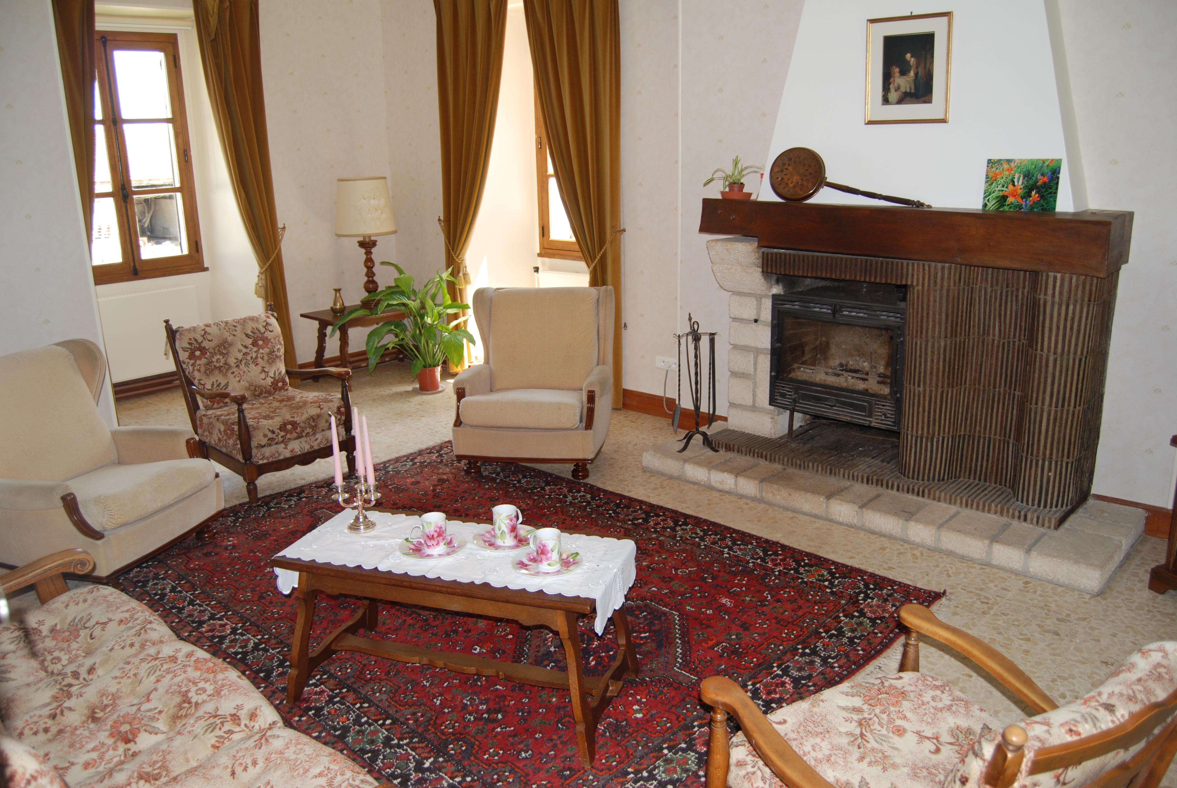 Le salon du gîte avec son grand tapis et ses nombreux sièges